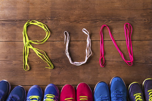 Five pairs of running shoes and shoelaces run sign on a wooden floor background
