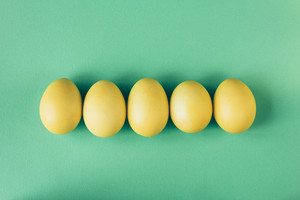 Five yellow eggs lie on a green background top view