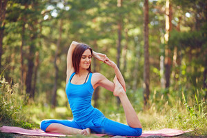 Flexible girl doing yoga exercise outdoors