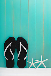 Flip Flops and starfish on teal wooden background