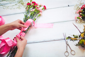 Florist hands tying carnation bouquet with pink silk ribbon