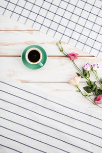 Flowers and cup of coffee between striped and plaid napkins on wooden background