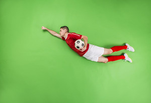 Flying football player in superman pose. Studio shot on a green backroung.