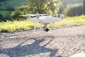 Flying helicopter drone with rised landing gears and camera, landing or taking off. Country road, green sunny nature.