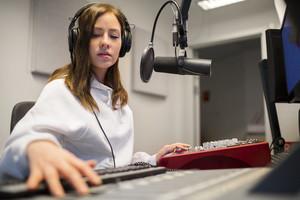 Focsued Radio Host Wearing Headphones In Studio