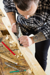 Focused craftsman working with plane on wood plank in workshop