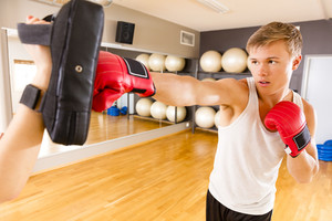 Focused man training boxing at the fitness gym