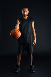 Focused young african basketball player giving ball isolated on a black background
