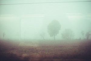 Foggy rural vintage filtered panorama view from a train window - isolation, loneliness, travel, nature concept