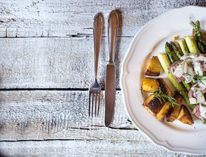 Food on a plate, fork and knife on a wooden background.