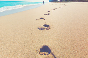 Footprints left in the sand of a tropical beach