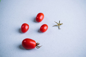 Four cherry tomatoes on the table with a blue surface closeup