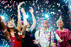 Four friends making having fun among confetti