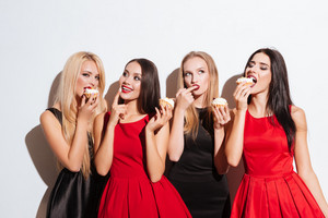 Four happy charming young women standing and tasting cupcakes over white background