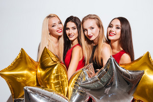Four happy gorgeous young women holding star shaped balloons over white background