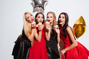 Four happy lovely young women standing and eating cupcakes on the party over white background