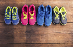 Four pairs of various running shoes laid on a wooden floor background
