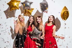 Four smiling attractive young women with star shaped balloons and confetti dancing and having party over white background