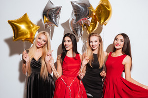 Four smiling beautiful young women with star shaped balloons standing together over white background