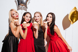 Four smiling gorgeous young women eating cupcakes on the party over white background