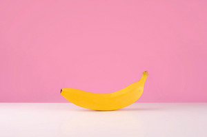 Fresh banana on table isolated over pink background
