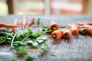 Fresh carrot with green leaves laid on white wooden table