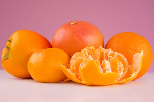 Fresh fruit peeled mandarin, persimmon, tangerine and orange on a table isolated on a pink background