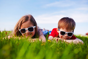 Friendly boy and girl in sunglasses relaxing in green grass