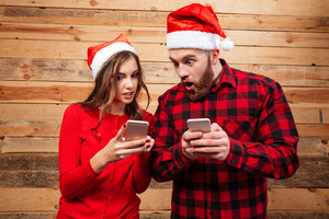 Friends in santa's hats with phones. looking at phones. shocked. wooden background