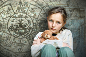 Frightened child with mayan calendar on her background.