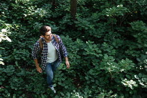 From above image of man in forest. looking away. smiling man.