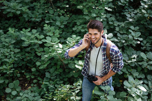 From above image of young guy in forest in the midst of plants. so smiling man. talking on the phone. guy with backpack and binoculars