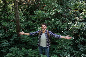 From above image of young man in forest. front view. spread your arms out to the sides. looking up