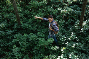 From above photo of man in forest. side view. showing finger away. looks back. in the middle of bushes
