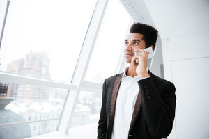 From below image of african business man in black suit standing near the window and talking on phone
