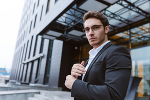From below image of Business man in suit and glasses standing sideways and looking at camera near the office