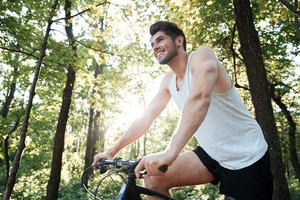 From below image of cyclist in forest. smiling man. side view