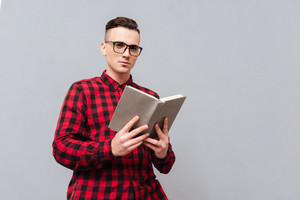 From below image of young serious man in glasses and red shirt reading book in studio. Isolated gray background