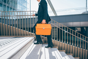 From the neck down view of a contemporary business walking upstairs in the city backlight, holding overnight bag - business, work concept