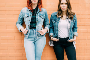 From the neck down view of two fashionable women leaning on a brick wall, wearing jeans clothes, with hands in pocket