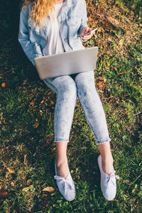 From the neck down view of young blonde woman sitting ont he grass using notebook and smart phone hand hold - technology, multitasking, social network concept