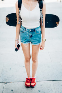 From the neck down view of young woman with skateboard and backpack, holding a smart phone and listening music with earphones - technology, sportive, music concept