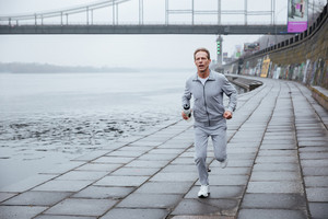 Front view of runner in gray sportswear running near the water. Full length image