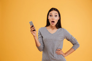 Front view of surprised model with phone and arm at hip. isolated orange background