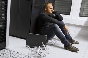 Frustrated and exhausted it engineer / consultant in a data center. Sitting apathetic in front of a server rack.