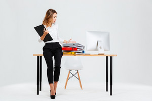 Frustrated stressed businesswoman standing at the office desk and holding folder