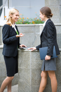 Full-growth portrait of two businesswomen discussing at a meeting in  front of the office building