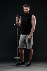 Full length athletic man with barbell. so happy man. isolated dark background