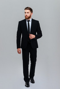 Full length bearded business man holding to suit in studio and looking aside. Isolated gray background