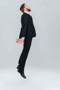 Full length bearded business man in black suit flying in studio. Side view. Isolated gray background